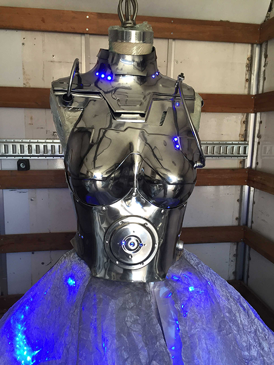 Vacuum-formed PETG upper body, gunmetal chrome finish, internal LEDs <br> Skirt built from lenticular film and polyester gauze, Bluetooth-enabled internal LEDs <br> Worn by Emanuela Postacchini & Styled by Tanya Gill, ICONHOUSE
